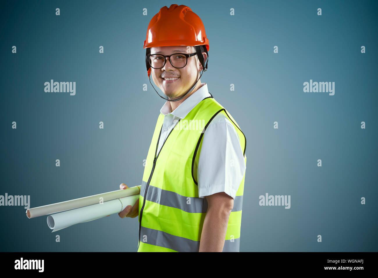 Portrait von lächelnden Bauarbeiter gegen farbigen Hintergrund Stockfoto