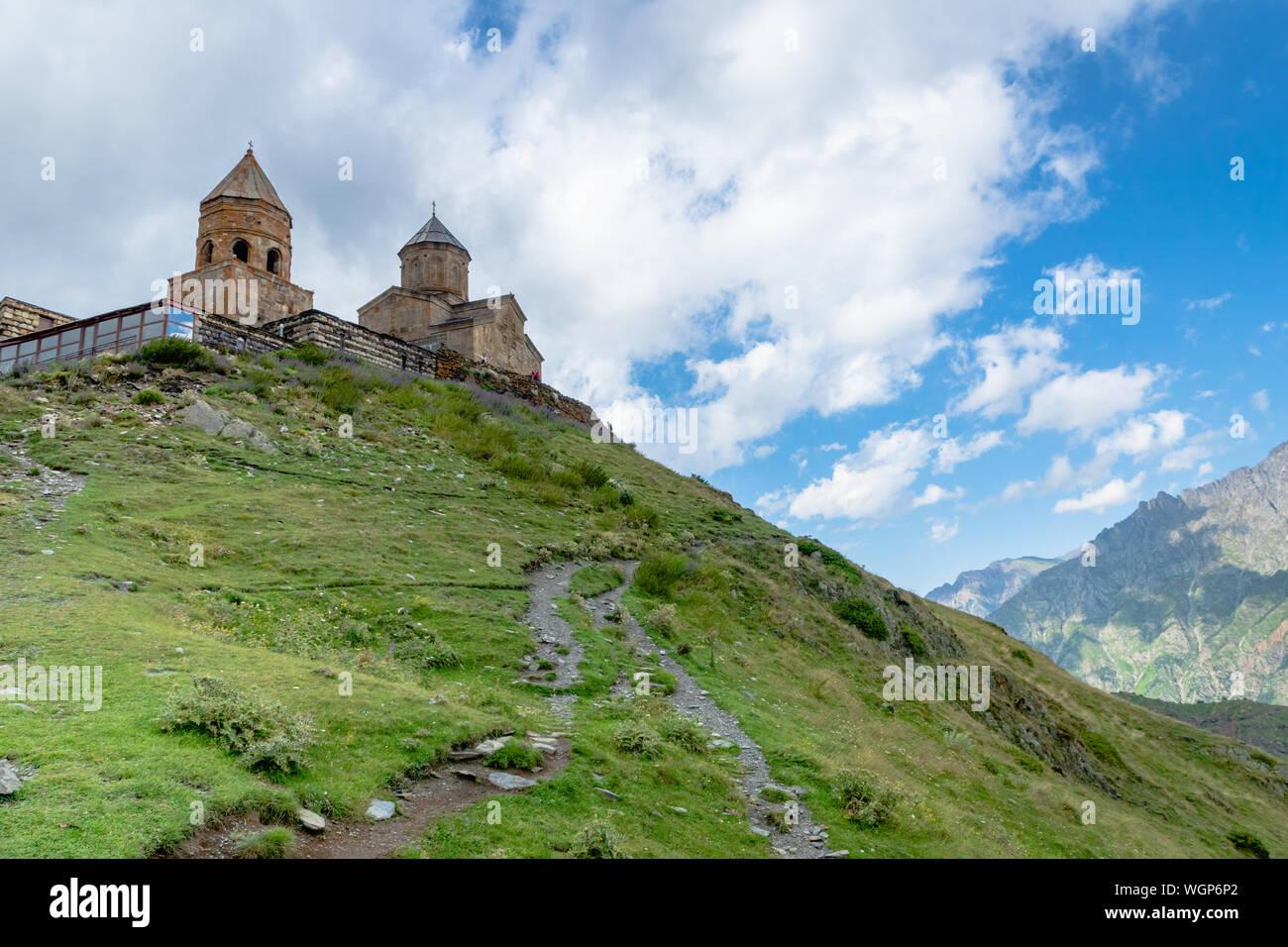 Gergeti Trinity Kirche oder Tsminda Sameba, dramatische landscaoe mit Wolken. Gergeti Kirche steht in der Nähe des Dorfes Gergeti in Georgien Stockfoto