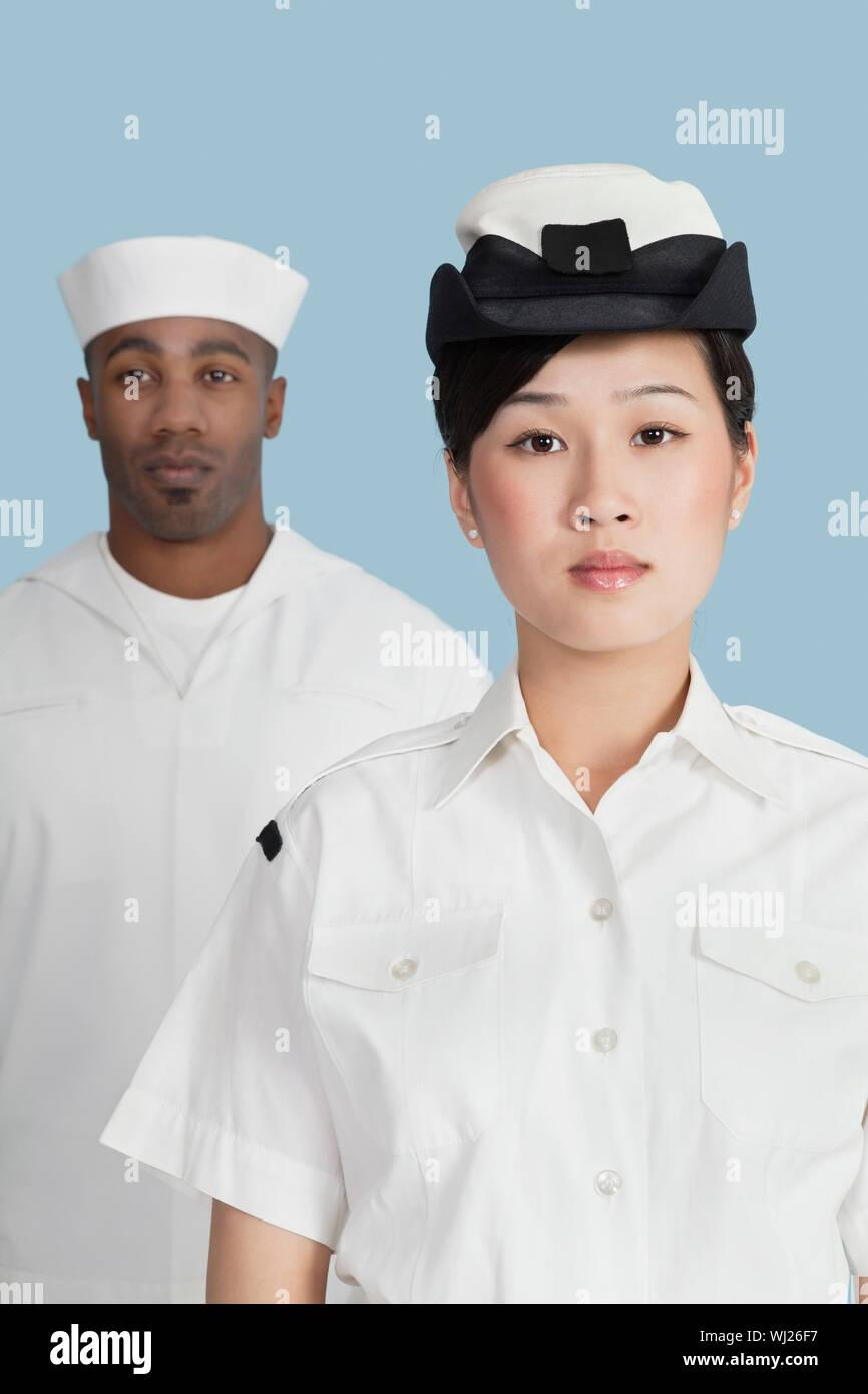 Portrait von zuversichtlich weiblichen Navy Officer vor männlichen Sailor über hellblauen Hintergrund Stockfoto