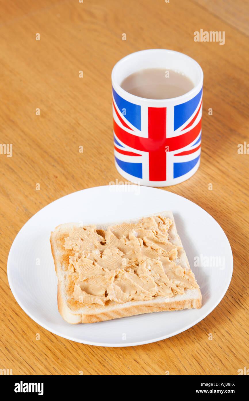Britische Kaffeetasse und Scheibe Brot mit Butter auf Tisch Stockfoto
