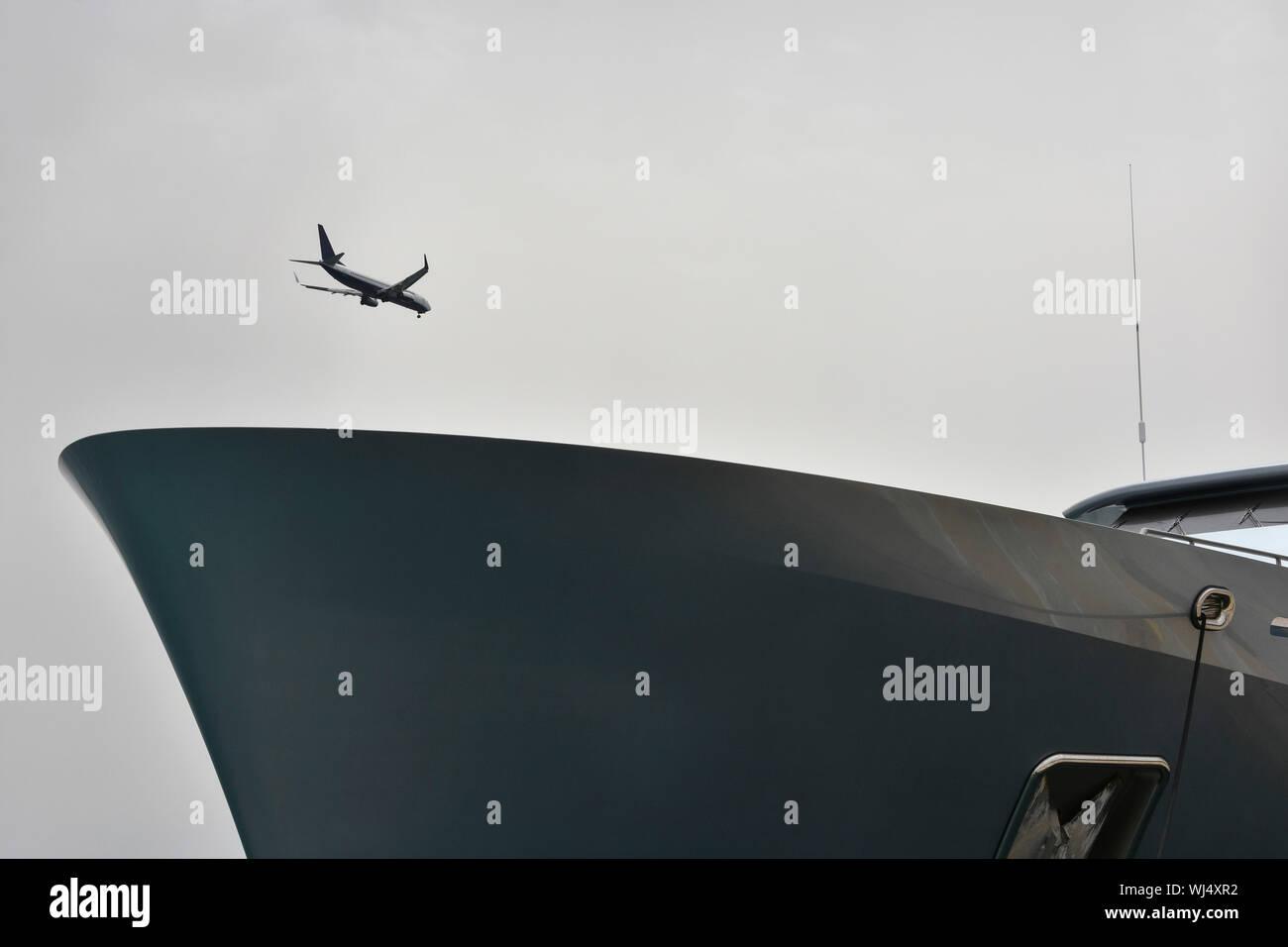 Flugzeug über Schiff bei bedecktem Himmel fliegen Stockfoto