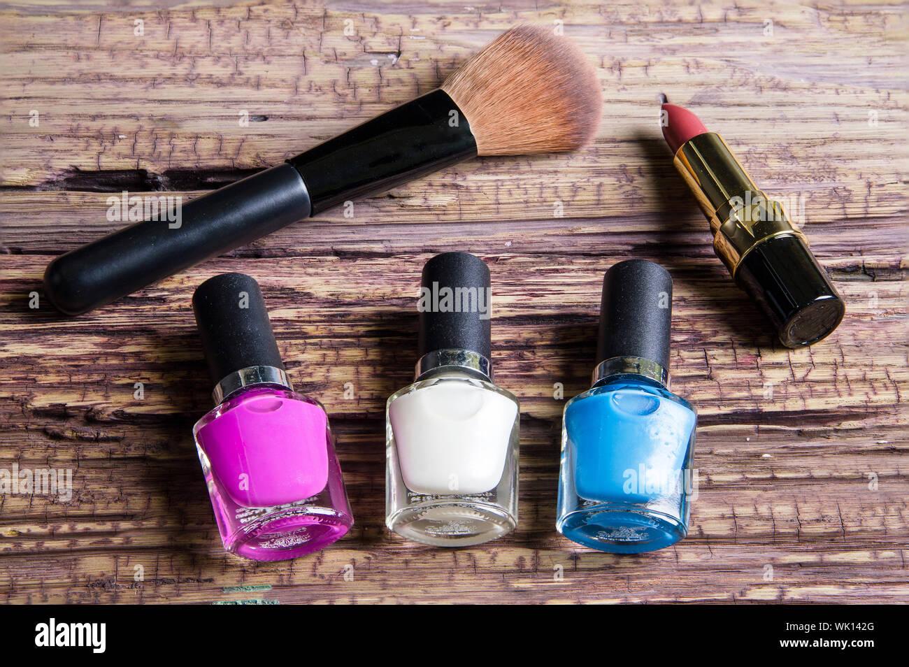 Hohe Betrachtungswinkel von Nagellack Flaschen mit Lippenstift und Make-up-Pinsel auf hölzernen Tisch Stockfoto