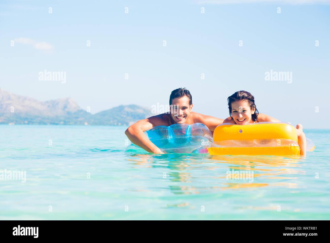 Porträt eines jungen Paares schwimmende aufblasbare Flöße im Meer gegen Sky Stockfoto