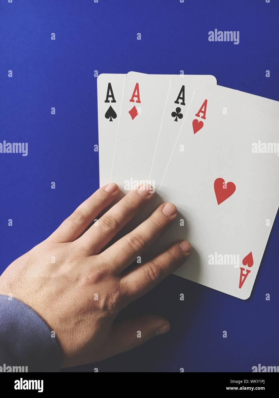 Hohe Betrachtungswinkel der Mann mit drei Assen Karten auf blauen Tabelle Stockfoto