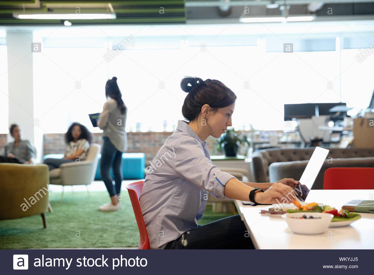Geschäftsfrau, Essen und Arbeiten am Laptop im Großraumbüro Stockfoto
