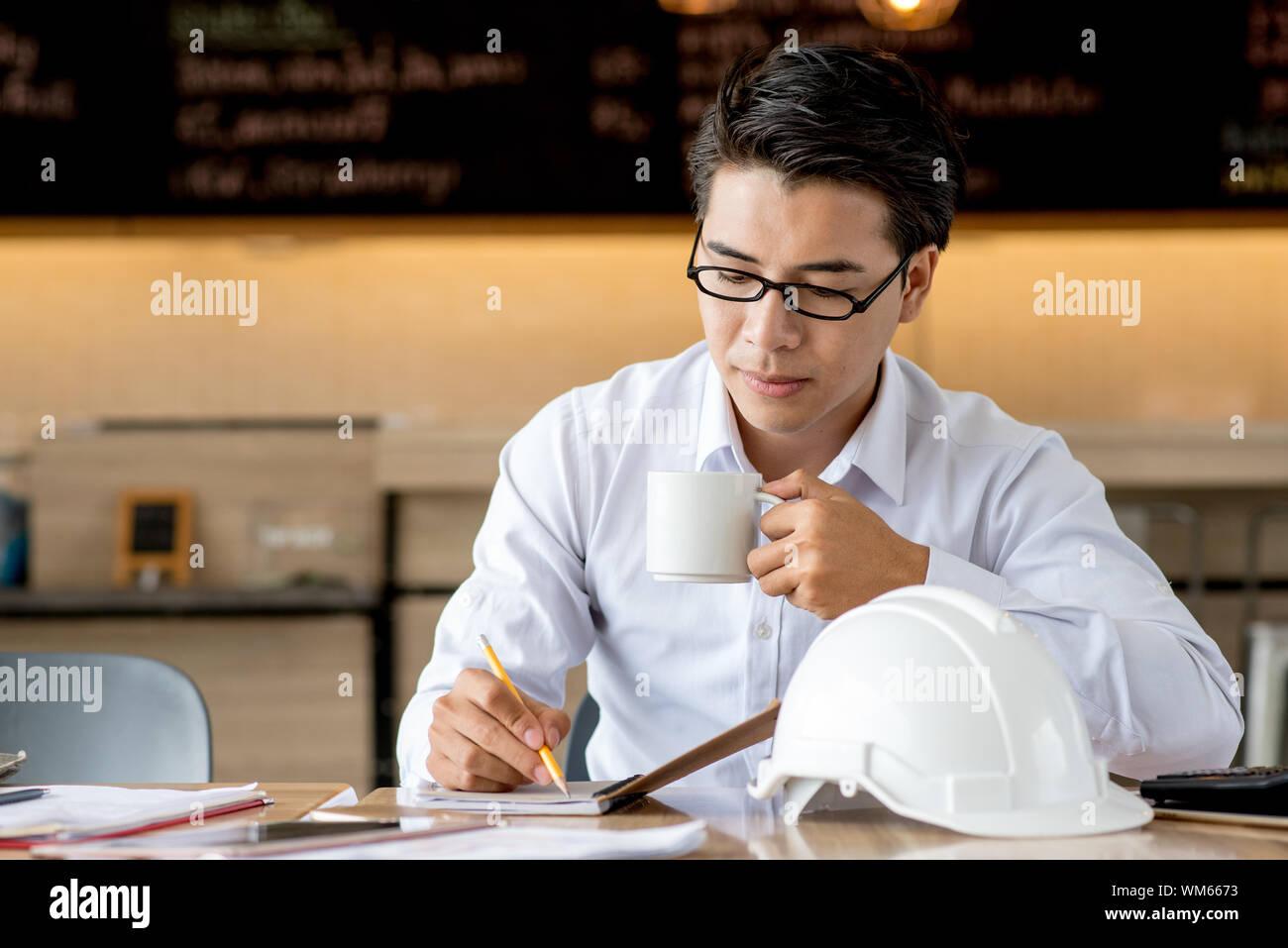 Mann hält Kaffee Tasse während der Arbeit auf dem Tisch im Cafe Stockfoto