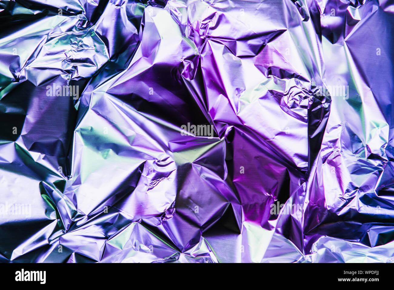 Zerknitterte bunte Folie Hintergrund. Abstrakte Muster mit Schatten. Neon Rosa und blauen Farbtönen. Stockfoto