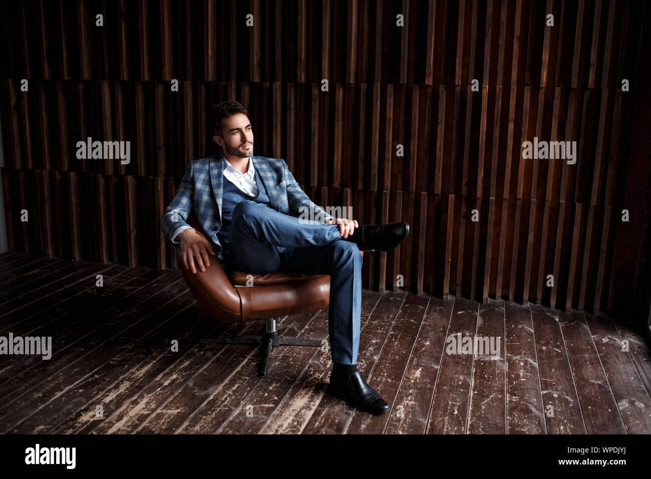 Junge erfolgreiche Geschäftsmann in einem blauen Anzug in einem Käfig sitzt in einem Ledersessel. junger Mann mit einem Bart lächelnd Stockfoto