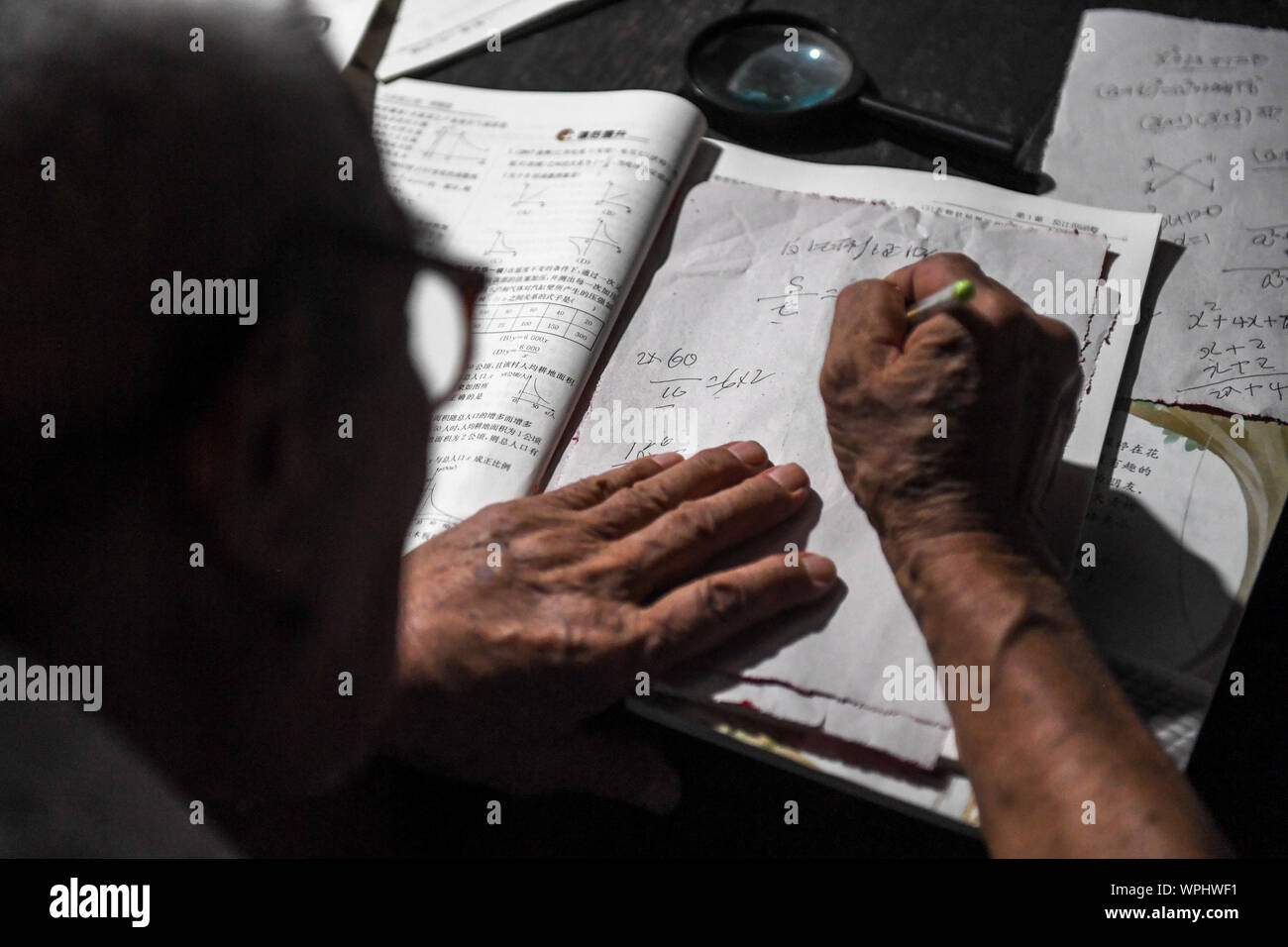 (190909) - CHANGSHA, Sept. 9, 2019 (Xinhua) - Tang Shangjun decodiert eine mathematische Frage zu Hause in Wuhan Dorf Anhua County in Yiyang City, Central China Provinz Hunan, Sept. 7, 2019. Ein Holzhaus steht allein in den tiefen Bergen durch einen lebhaften grünen Decke von Bäumen bedeckt, nicht nur als Wohnung, sondern auch als ein Klassenzimmer, wo Tang Shangjun Nachhilfe Studenten Seit mehr als 20 Jahren. Tang, einem 92-jährigen ländlichen Lehrer, nachhilfe begonnen, die Kinder durch ihre Eltern mit Migrationshintergrund kostenlos Links in Wuhan Dorf im Jahre 1997, 10 Jahre nachdem er zog sich von der Lehre in Anhua Coun Stockfoto