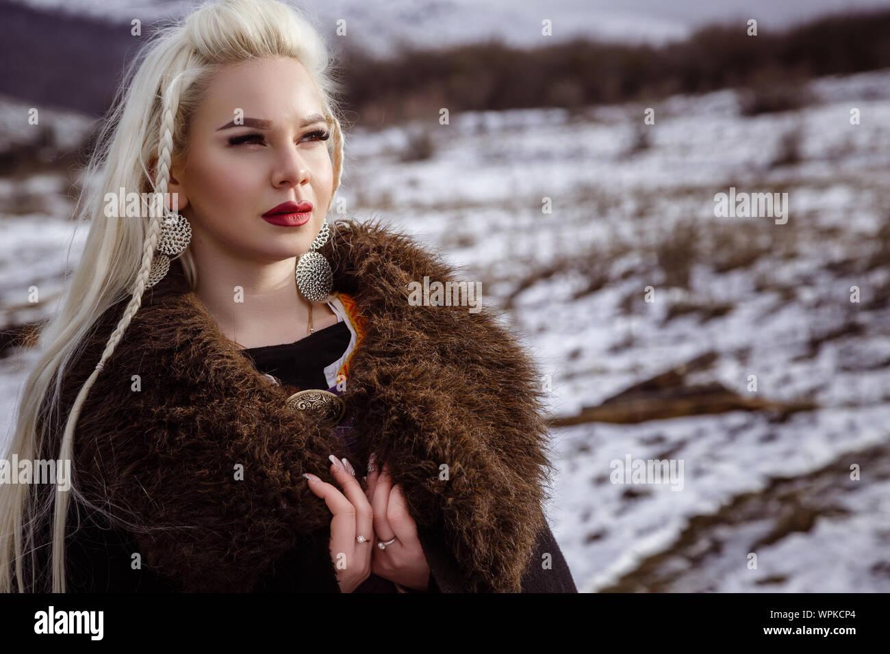 Im freien Porträt der Schönen wütend skandinavischen Krieger Ingwer Frau in traditioneller Kleidung mit Pelzkragen, mit Schwert in der Hand und Holz- V Stockfoto