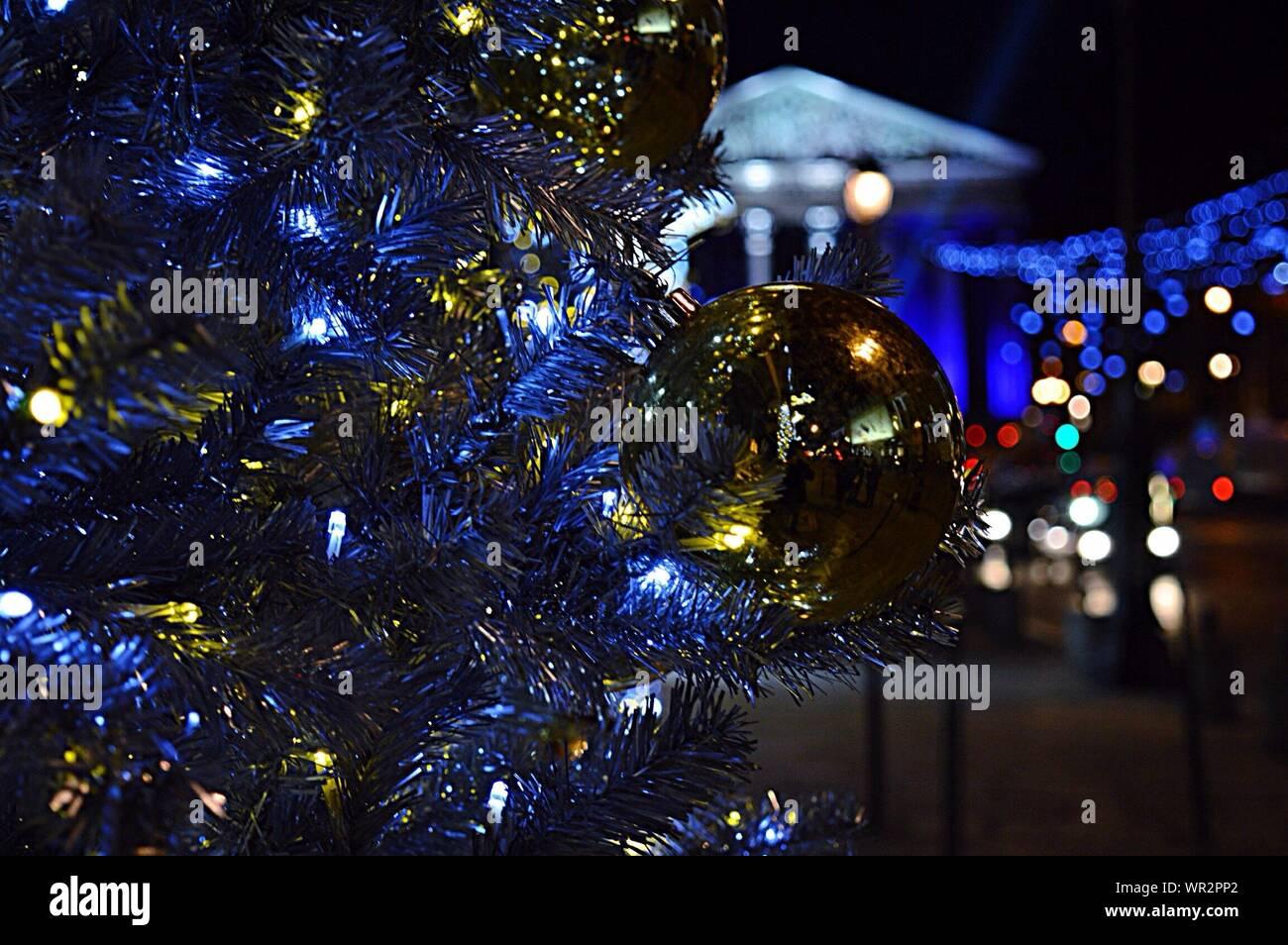 Goldene Christbaumkugel hängen von künstlichen Weihnachtsbaum in der Nacht Stockfoto