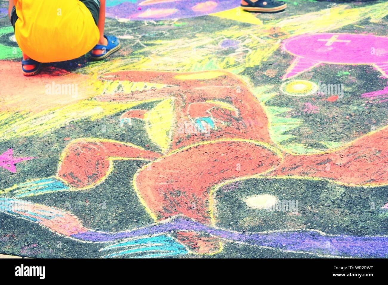 Ansicht der Rückseite des Jungen zusammengekauert auf lackierten Straße Stockfoto