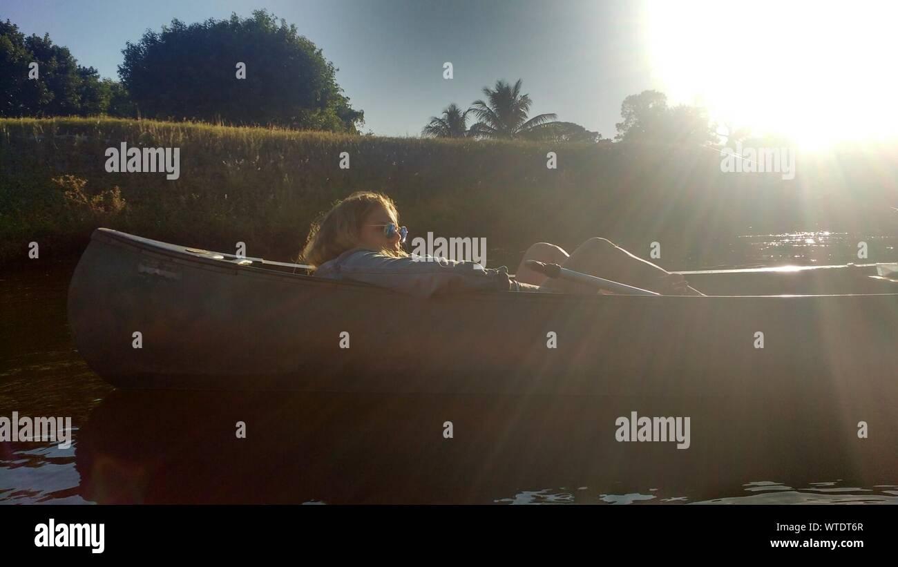 Junge Frau sitzt im Boot auf dem See Stockfoto