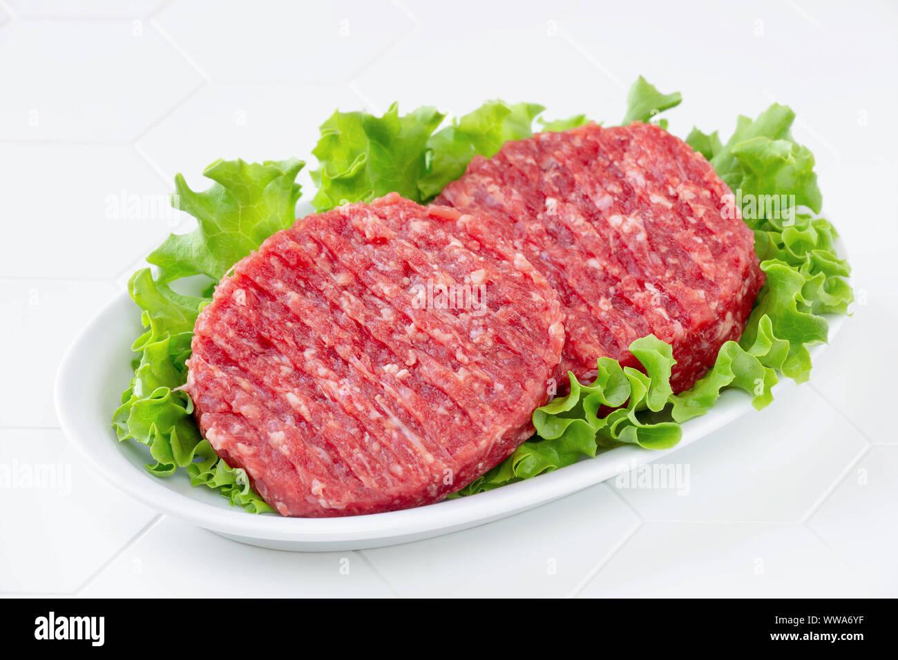 Rohes Fleisch Rindfleisch Burger auf einem weißen Teller Hackfleisch Stockfoto