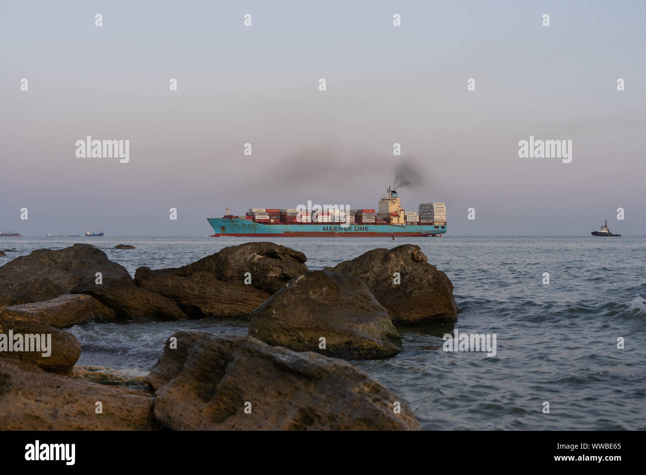 Eine schwere Containerschiff mit Cargo tritt in den Hafen von Tug. Hafen von yuzhny. Küsten Steine im Vordergrund. Selektive konzentrieren. 2019.09.01. Odessa. Ukrai Stockfoto