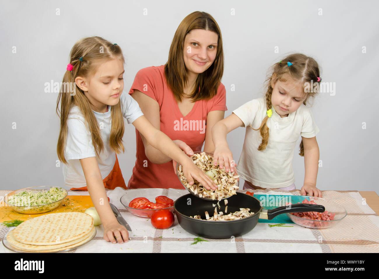 Zwei kleine Mädchen auf dem Küchentisch mit einem Eifer zu helfen, ihre Mutter die Pilze aus der Platte in die Pfanne gießen Stockfoto