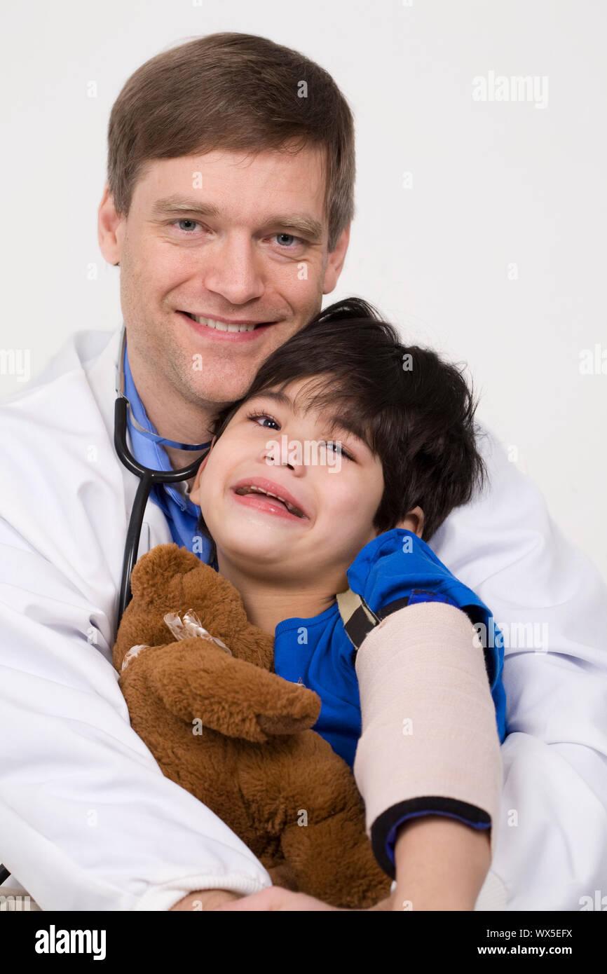 Männlicher Arzt Anfang der vierziger Jahre beruhigende fünf Jahre alte behinderte Patienten während Büro besuchen Stockfoto