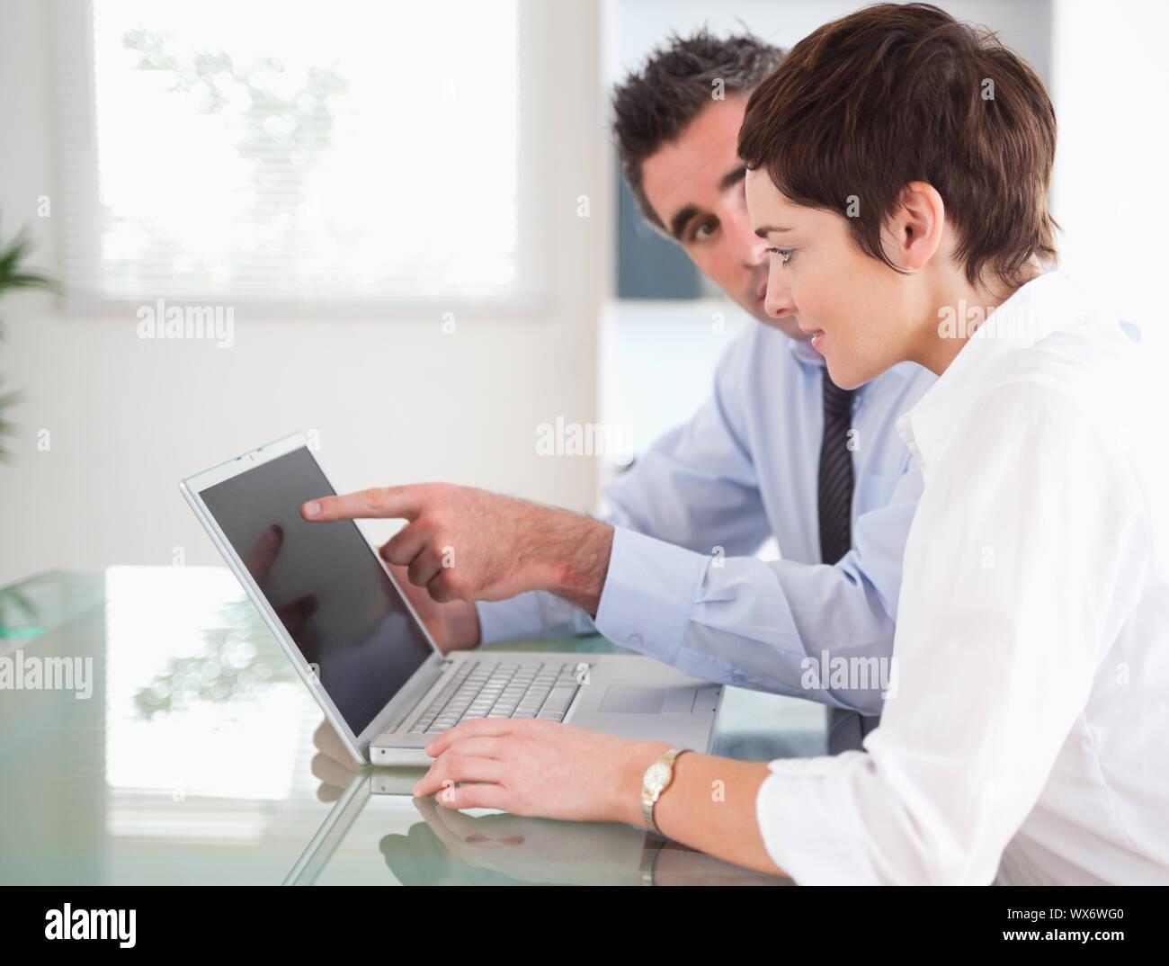 Mann zeigt auf etwas zu seiner Sekretärin auf einem Laptop in einem Büro Stockfoto