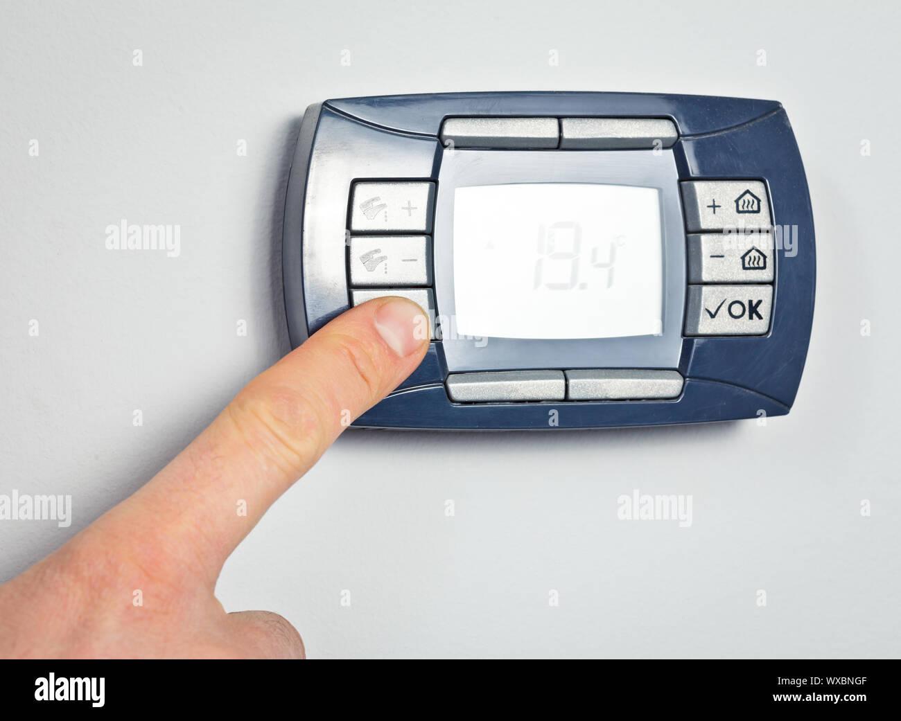Finger drücken der Taste auf ein digitales Thermostat Control Panel Stockfoto