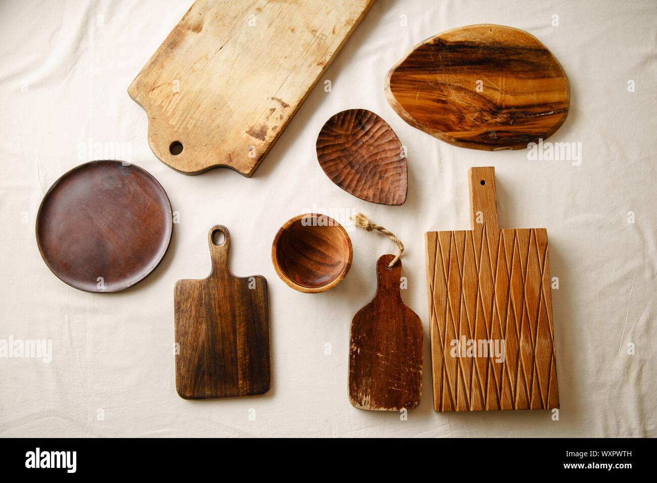 Verschiedene Holz- Geschirr. Schneidbretter, Teller und Schüssel auf Leinen Tischdecke Stockfoto