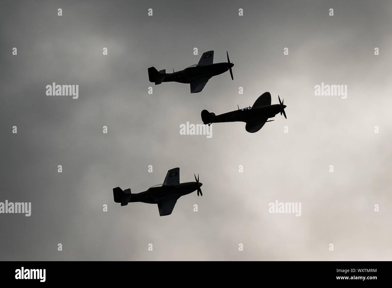 Die Vintage-themed Goodwood Revival. Großbritanniens größte jährliche Classic Car Show. Rolls Royce Merlin Spitfire Mk IX (Mitte) und zwei P51D Mustang Kampfflugzeuge in den Himmel drei Tage der Aktion ab, was einst RAF Westhampnet. UK. Stockfoto
