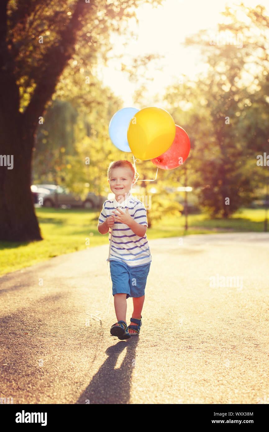 Cute adorable kleine Kaukasischen jungen Kleinkind Kind mit bunten Luftballons im Park Outdoor. Kid genießen zu spielen. Happy birthday Urlaub Feier. Stockfoto