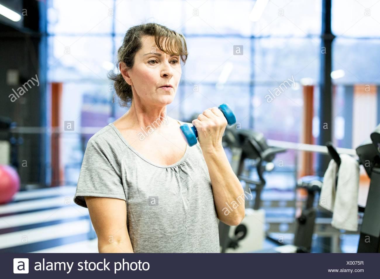 EIGENTUM FREIGEGEBEN. -MODELL VERÖFFENTLICHT. Ältere Frau mit Hantel im Fitness-Studio. Stockbild