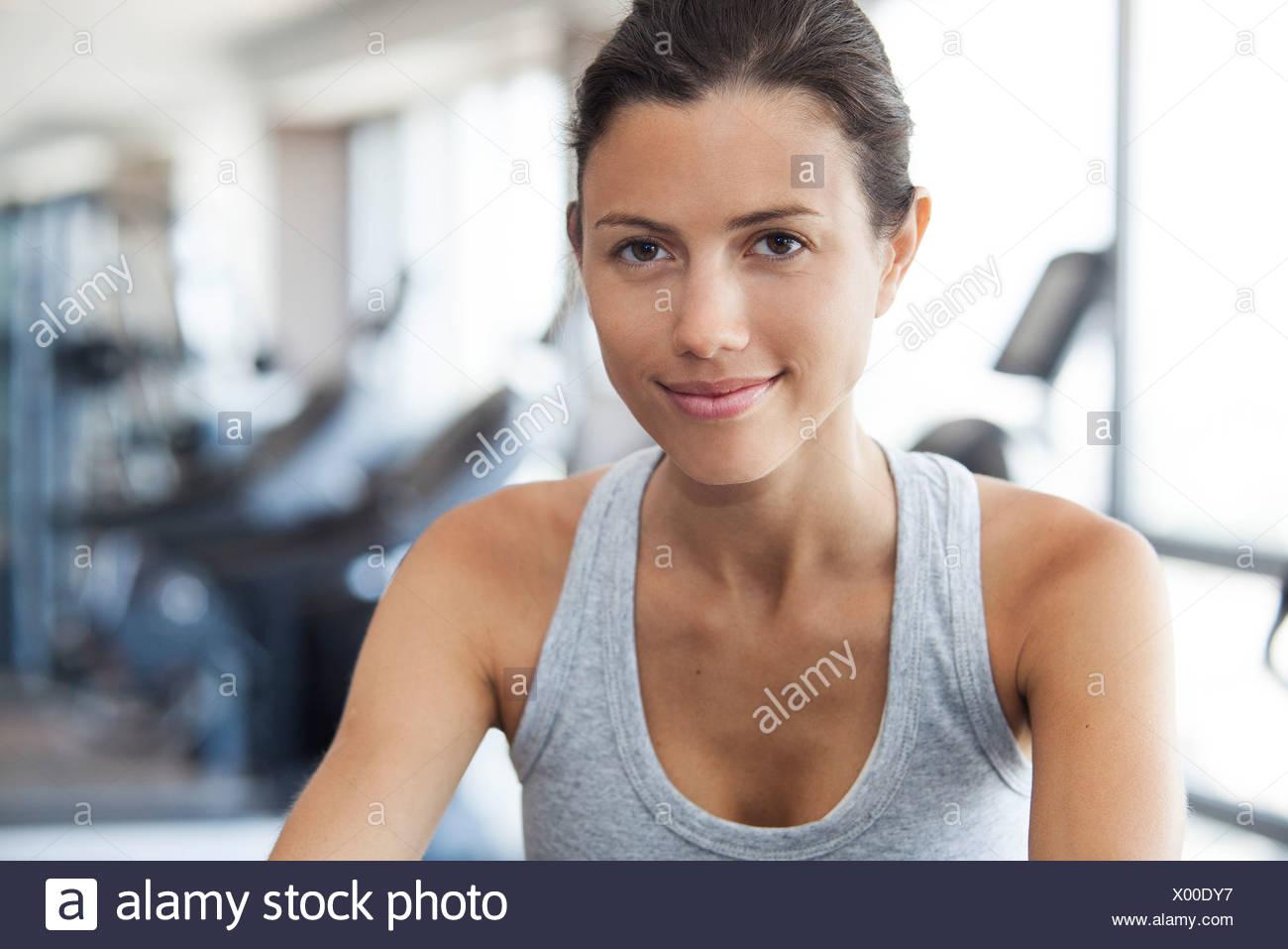 Junge Frau mit Heimtrainer in Turnhalle Stockfoto