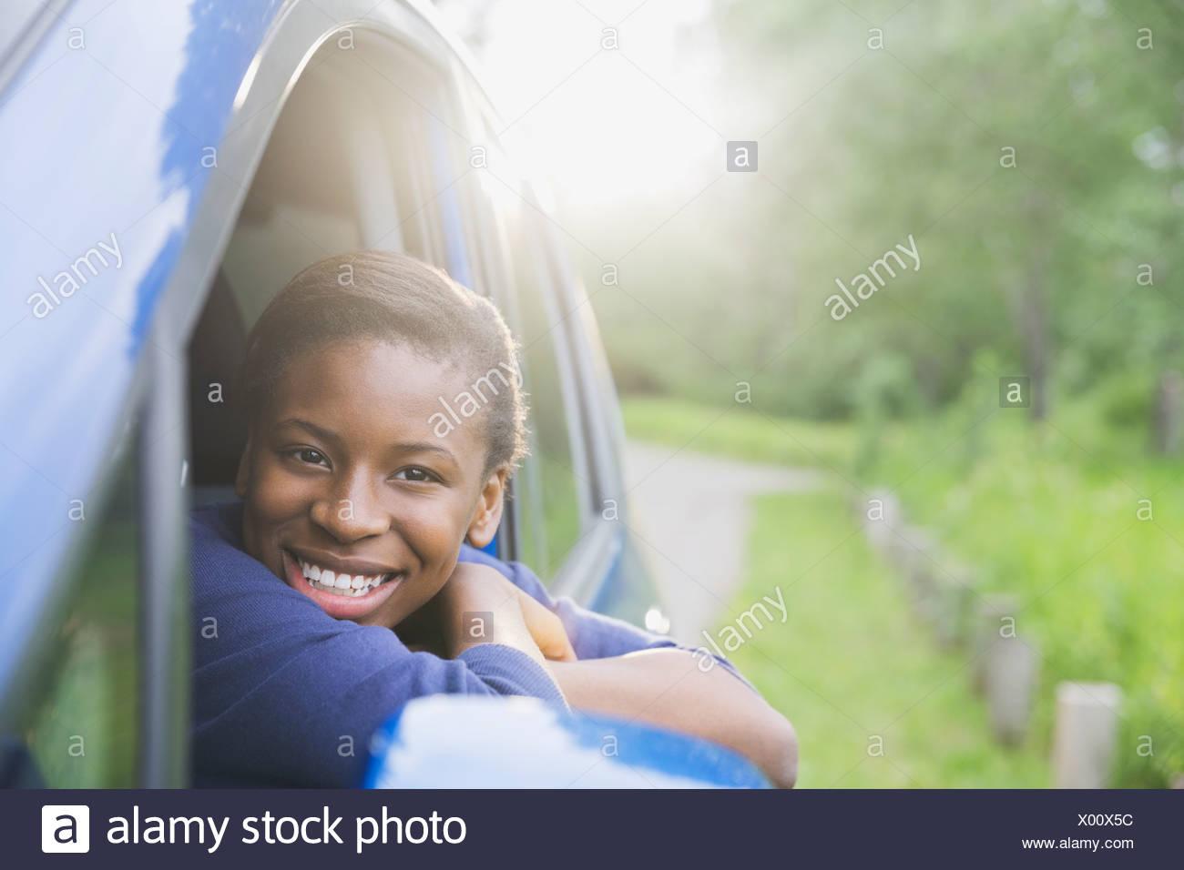 Lächelnde Teenager-Mädchen aus dem Autofenster Stockbild
