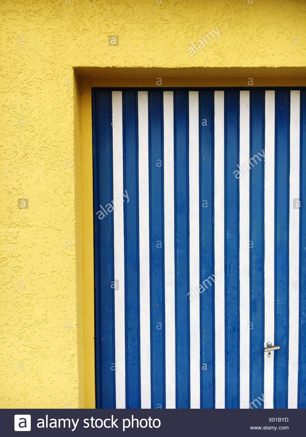Blau gestreifte Tür auf gelbe Haus Stockbild