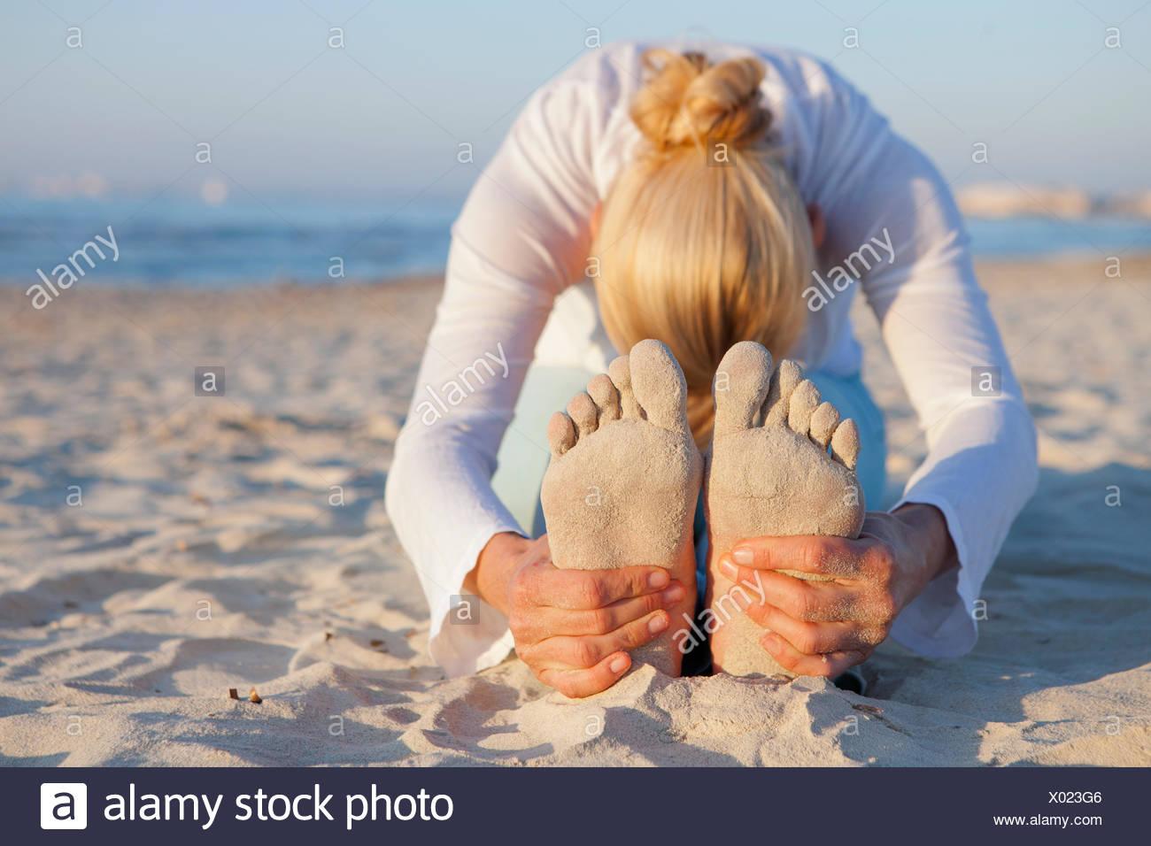 Frau tut Yoga Gebet Strecke am Strand Stockbild