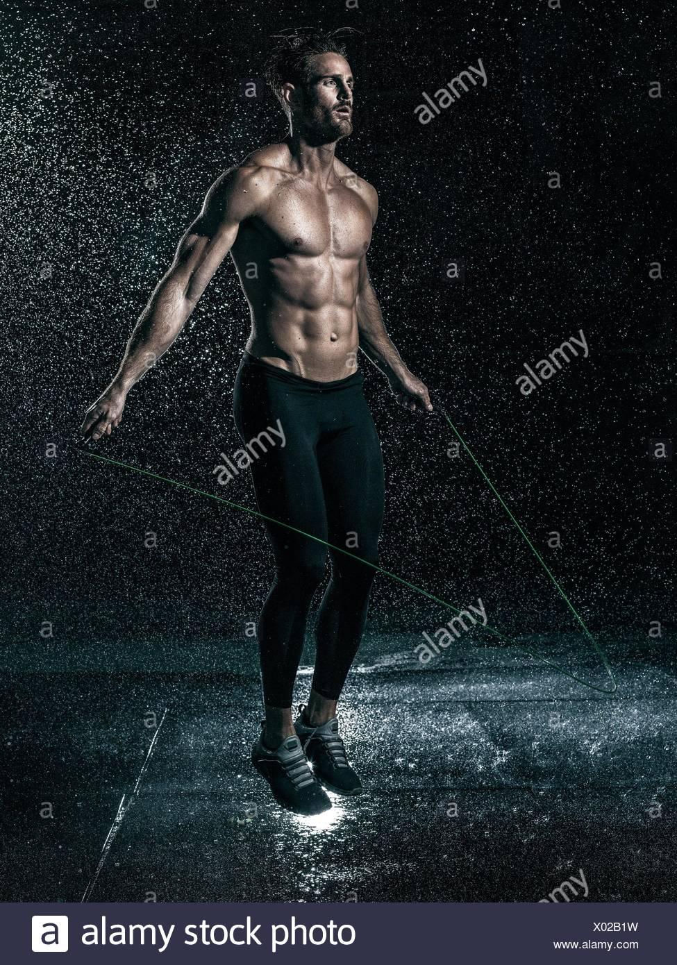 Mitte erwachsenen Mannes im Freien, überspringen in Regen Stockbild