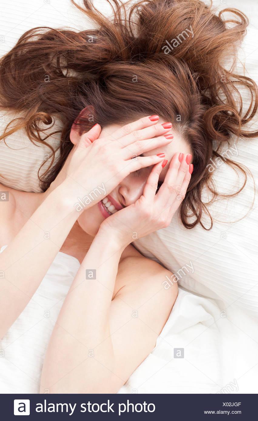 MODEL Release Frau liegend mit Händen über Gesicht lächelnd. Stockbild