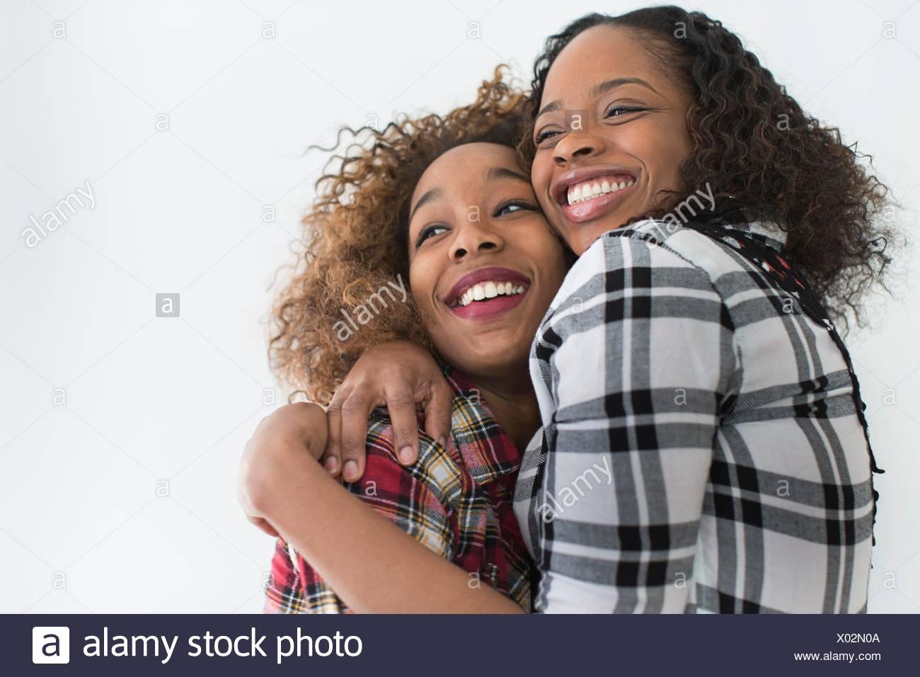 Studio-Porträt von zwei jungen Freundinnen umarmen Stockbild