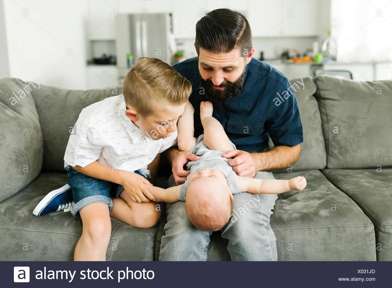 Vater und Kind (6-7) spielt mit Baby (6-11 Monate) im Wohnzimmer. Stockbild