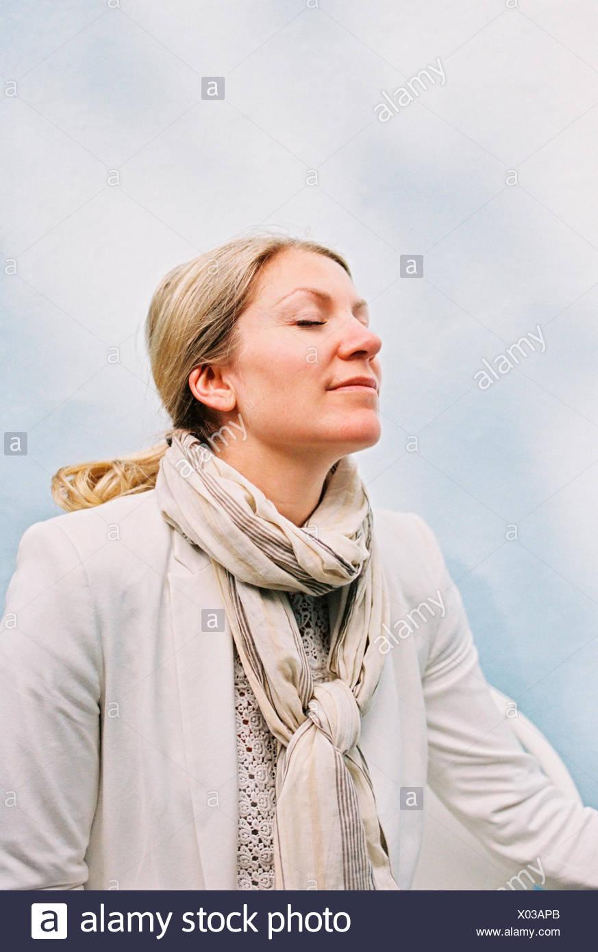 Eine Frau mit blonden Haaren sitzen mit geschlossenen Augen und ihr Kopf schräg zurück, das Gefühl der Sonne auf ihrem Gesicht. Stockbild