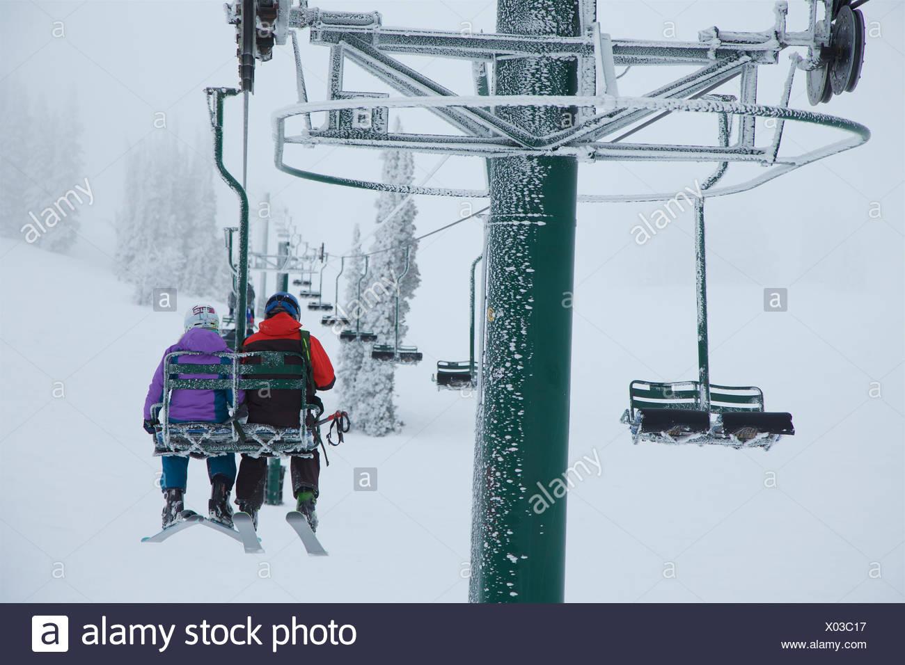 Geschwister, die Sesselbahn Skifahren in stürmischen Bedingungen zu gehen. Stockbild