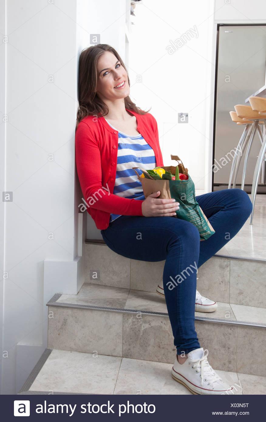 Junge Frau sitzt auf Küche Schritt mit Einkaufstüte Stockbild