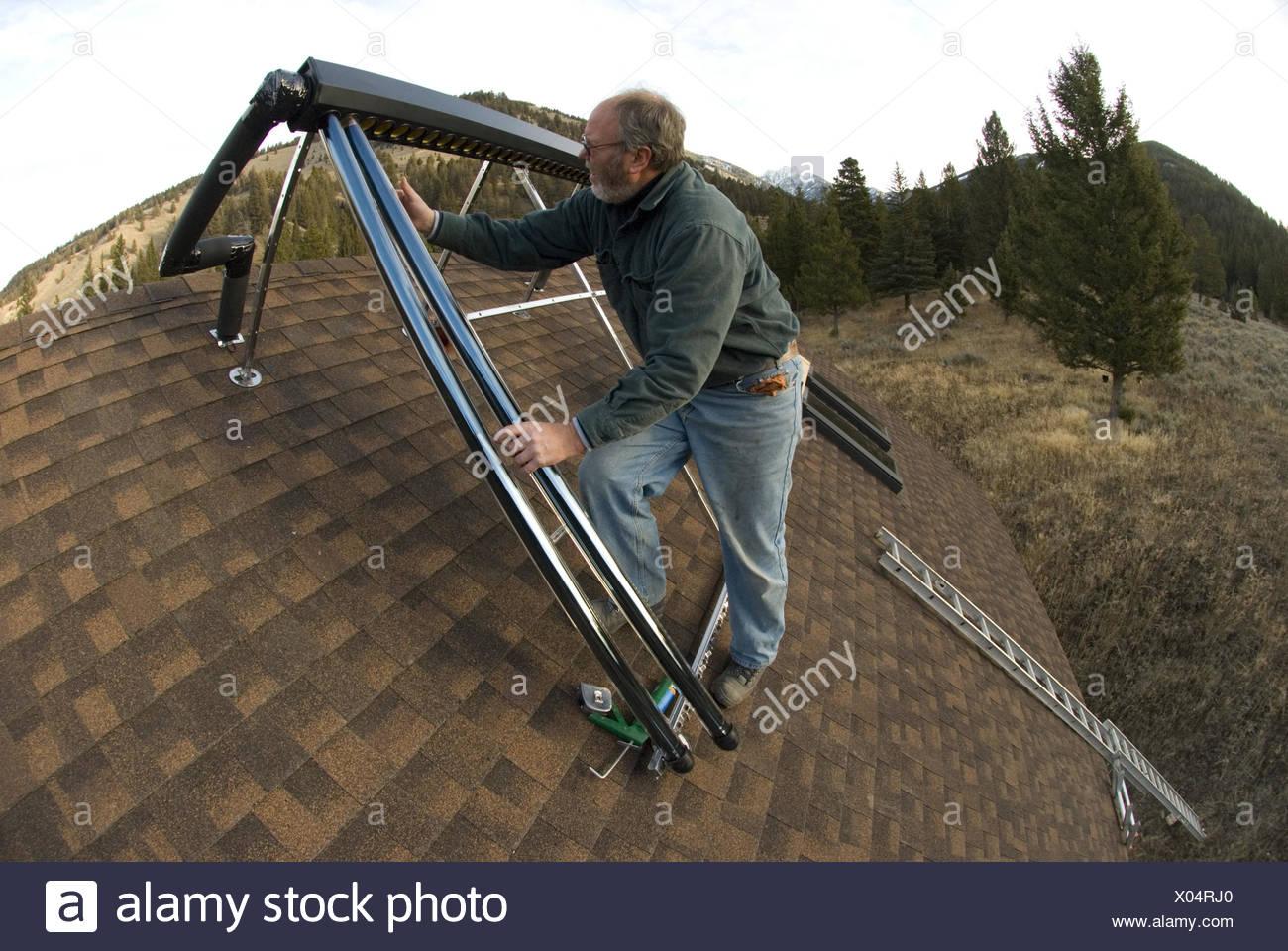 Ein Arbeiter wird eine solar-Warmwasser-System installiert Stockfoto ...