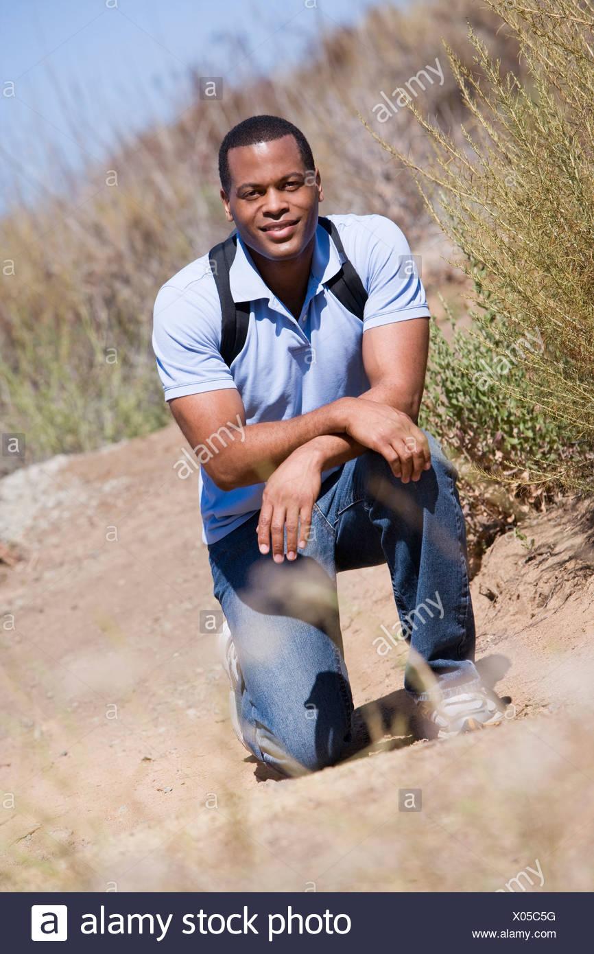 Mann kauert auf Pfad zum Strand lächelnd Stockbild