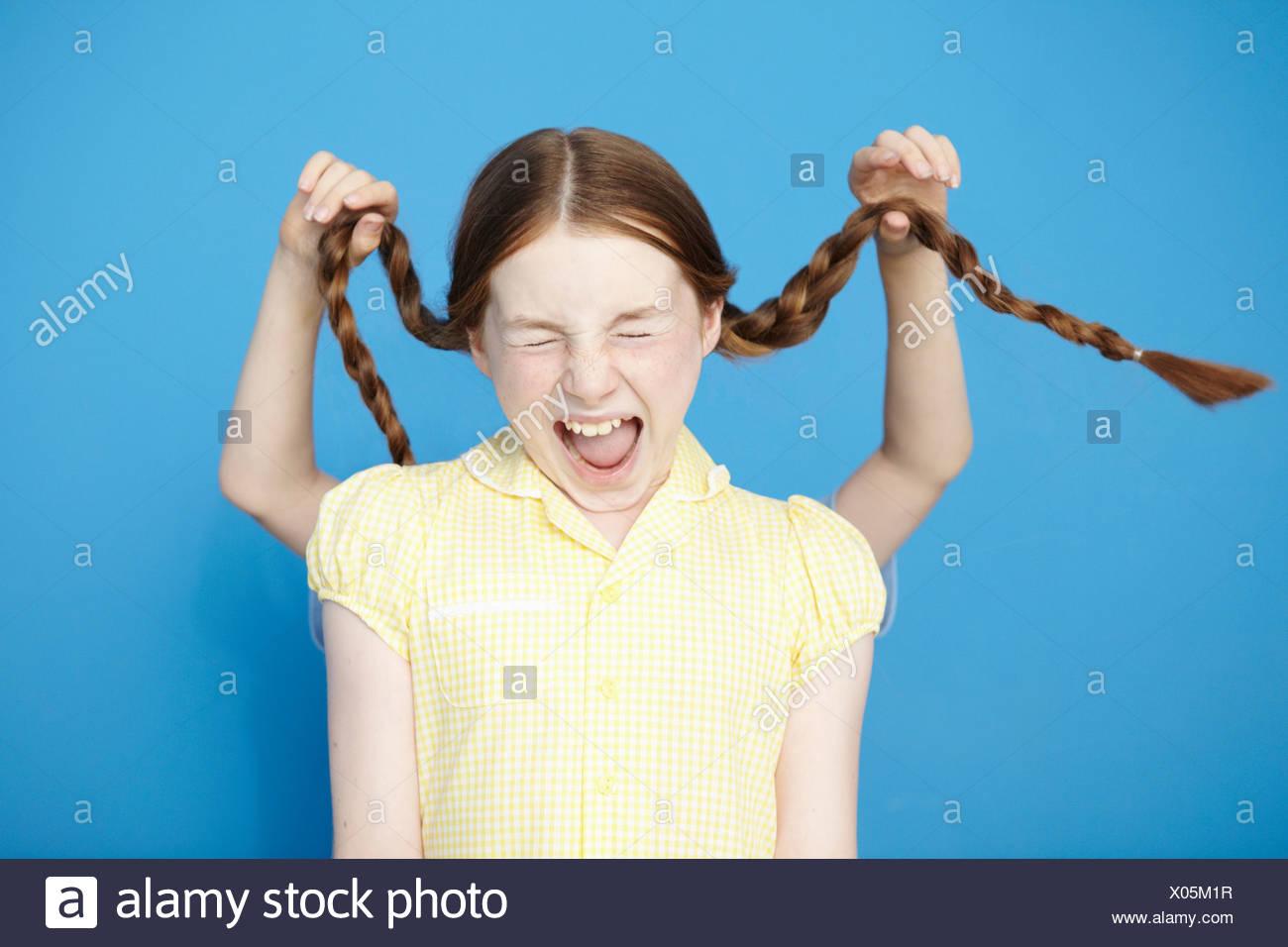 Mädchen Kleid gelb Schule, junge hinter ziehen ihre Zöpfe Stockfoto