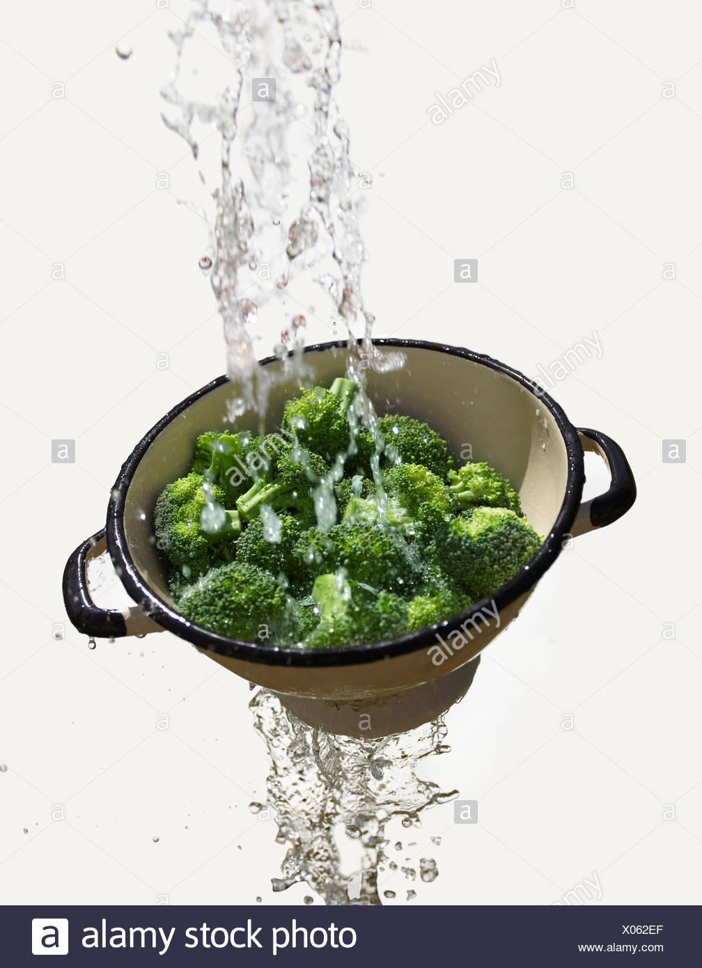 Wasser fällt durch das Sieb mit frischem Brokkoli Stockbild