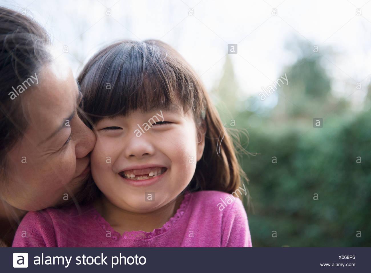 Mädchen wird von ihrer Mutter im Garten auf die Wange geküsst Stockbild