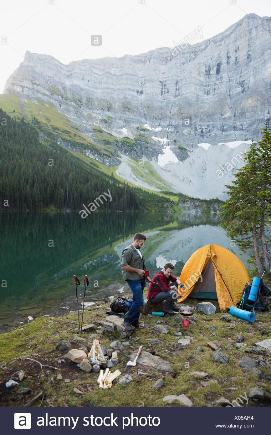 Männliche Freunde auf abgelegenen Berg am See Campingplatz camping Stockbild