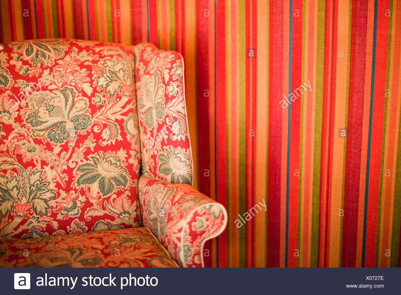 Floral gemusterte Stuhl gegen gestreifte Wand Stockbild