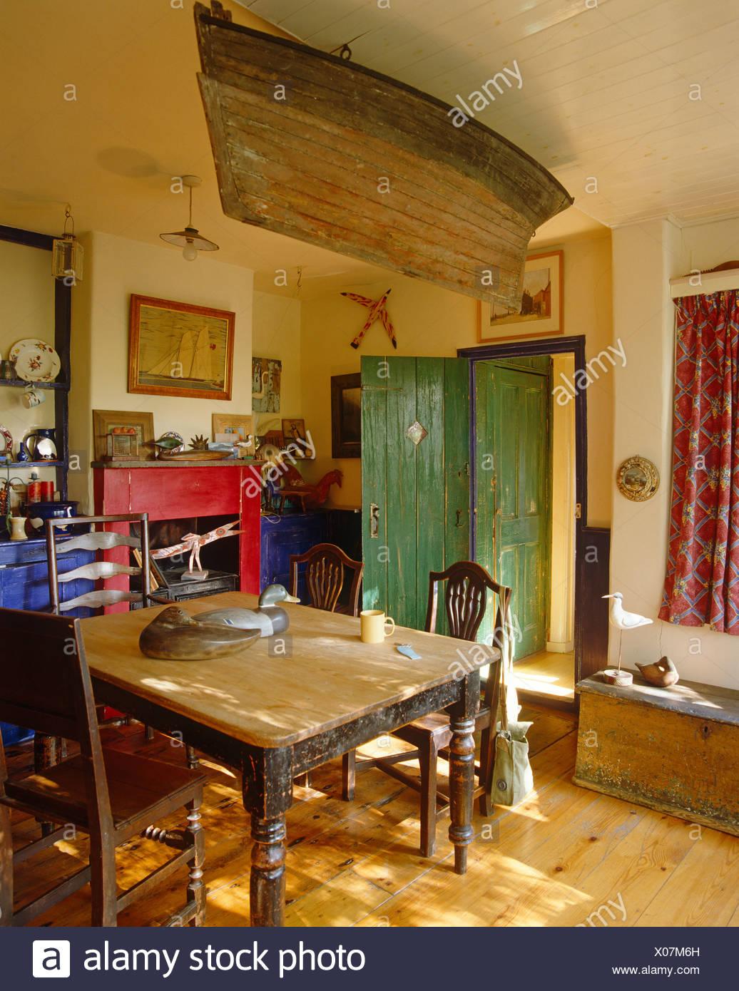 Rustikaler Holztisch Und Stühle Unter Ruderboot Ausgesetzt Von Der Decke In  Rustikales Landhaus Esszimmer Mit Holzboden