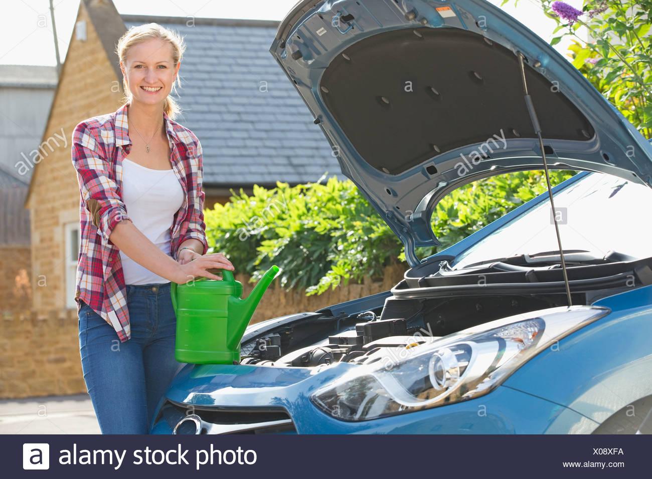 Frau Autokühler mit Wasser füllen Stockbild
