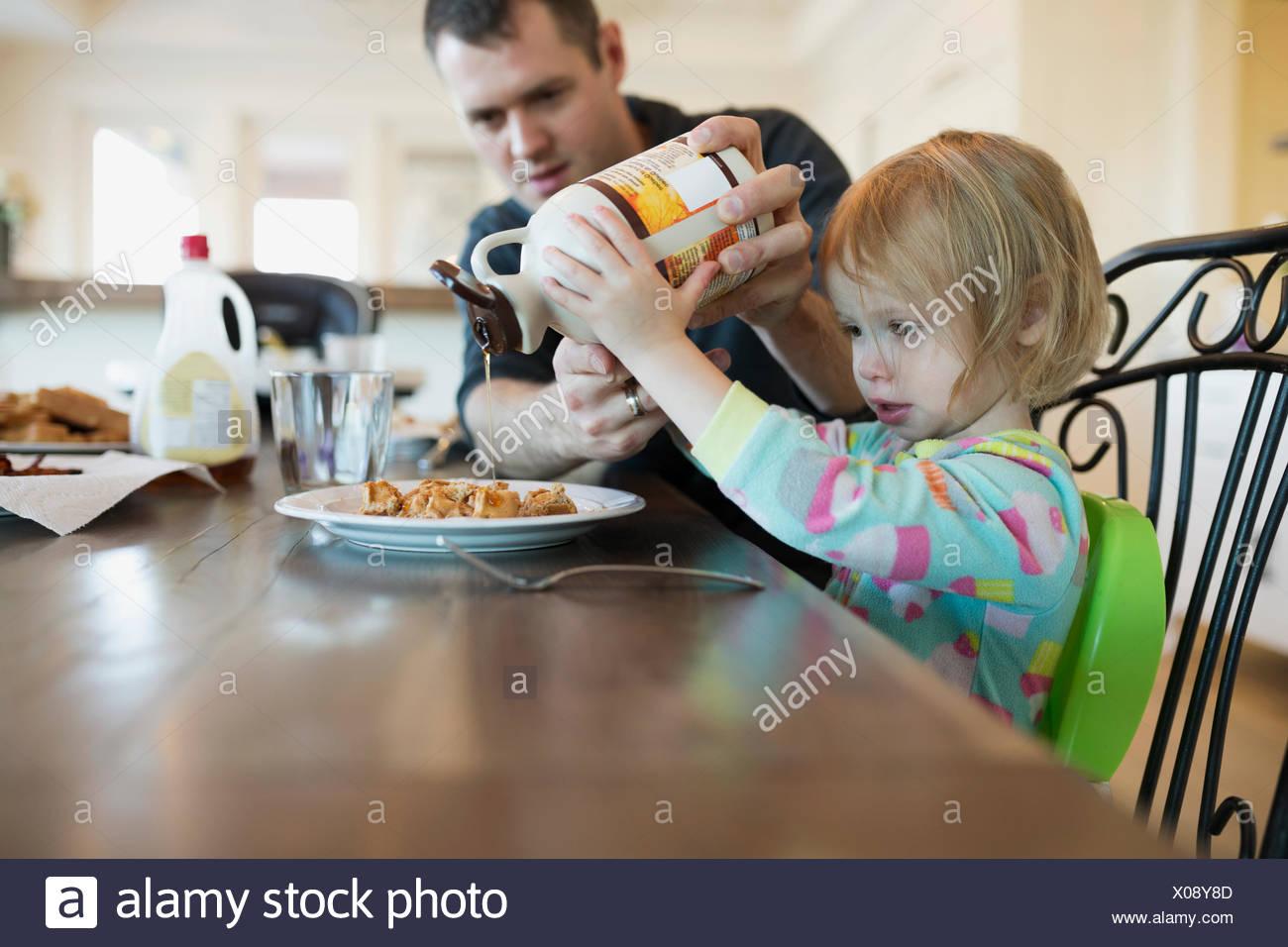Vater Tochter Gießen Ahornsirup auf Waffeln zu helfen Stockbild