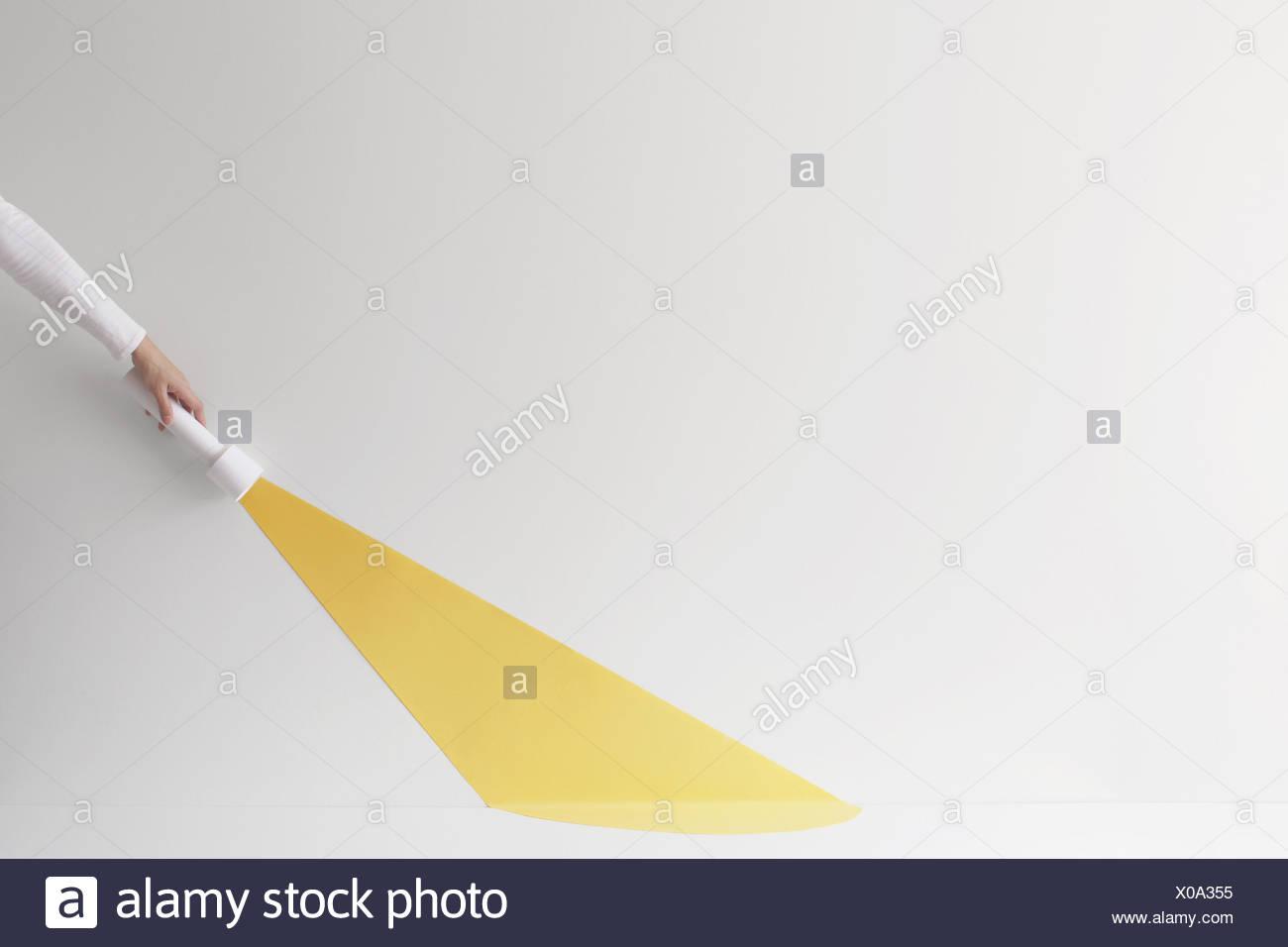 Konzeptionelle Hand hält eine Fackel mit Lichtstrahl Stockbild