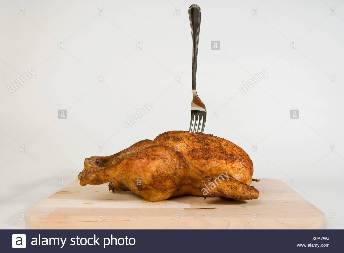 Eine Gabel in ein gebratenes Huhn stecken Stockbild